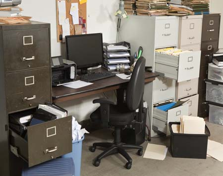 Very messy office with piles of files.